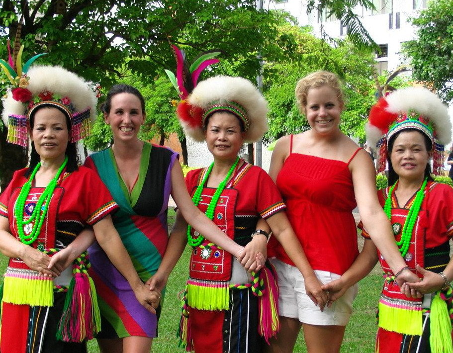 photo: Two foreign students dance with three Taiwanese aborigines wearing traditional clothes.